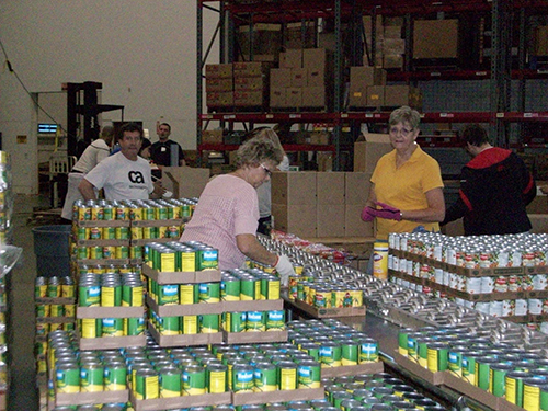 Women working to package canned goods in a warehouse