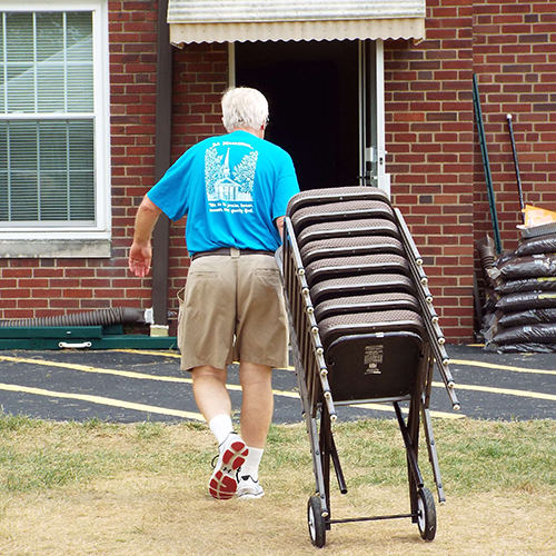 An older gentleman, moving a stack of chairs near the church building.
