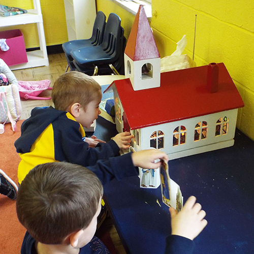 Two young boys playing with a church dollhouse toy.