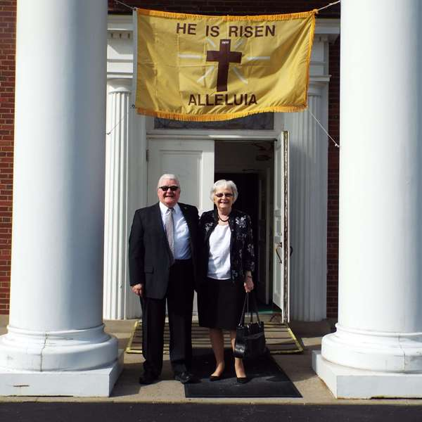 An older couple standing in front of the front doors of the church