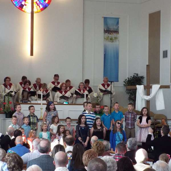 Kids singing in front of the church