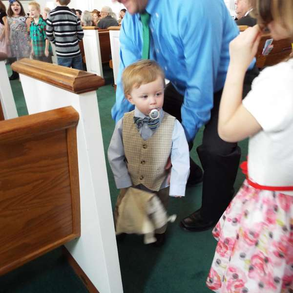 A little boy in church, dressed up in a suit with a bow tie, holding a teddy bear