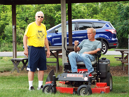 Two men outside, one sitting on a riding lawnmower.