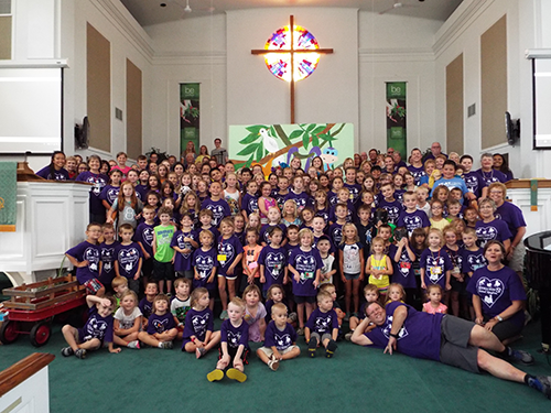 The entire VBS group, including kids and adults, posing in the front of the altar for a photo