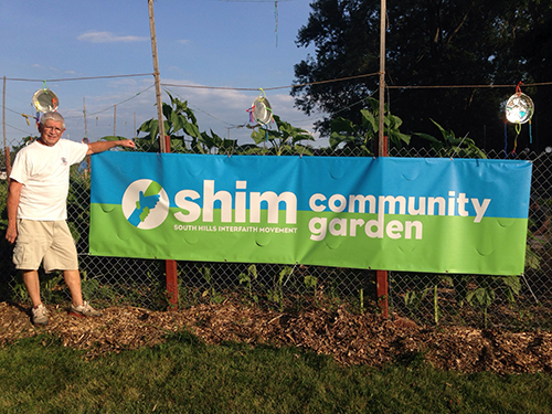 "A banner on the garden fence that reads ""SHIM Community Garden"""